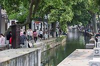 Suzhou, Jiangsu, China.  Visitors Walking along Canal Passing through Tongli Ancient Town near Suzhou.