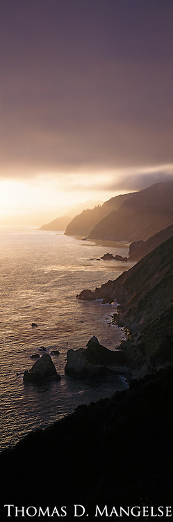 The setting sun silhouettes the Big Sur coast in California.