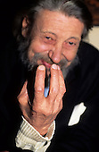 Prague, Czech Republic. Smiling elderly bearded man with his arthritic fingers in front of his face.