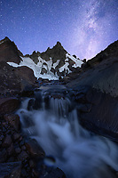 The milky way frames a mountain peak on a remote moraine filled with melting glacier and icebergs in the Thee Sisters Wilderness.