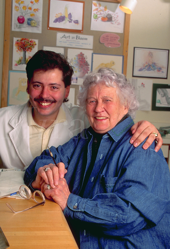 Portrait of a smiling senior woman and male caregiver at a nursing home.
