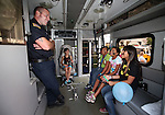 Carson City Fire Department Firefighter/Paramedic Porter talks with, from left, Alexia Gomez, 9, Betsy Flores, 12, Yahayra Soriano, 11, and Jazzy Soriano, 11, at the 11th annual National Night Out hosted by the Carson City Sheriff's Office in Carson City, Nev., on Tuesday, Aug. 6, 2013. <br /> Photo by Cathleen Allison