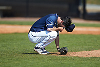 Queens Royals relief pitcher Garrett Crisp (24) says a prayer behind the mound during game two of a double-header against the Catawba Indians at Tuckaseegee Dream Fields on March 26, 2021 in Kannapolis, North Carolina. (Brian Westerholt/Four Seam Images)