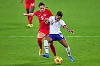 18th February 2021, Orlando, Florida, USA;  United States defender Crystal Dunn (19) battles with Canada forward Evelyne Viens during a SheBelieves Cup game between Canada and the United States on February 18, 2021 at Exploria Stadium in Orlando, FL.