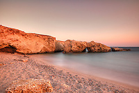 Wild beauty beach with eaten by the sea cliffs and unique caves in Karpathos, Greece