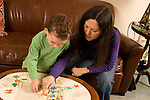 mother and 3 year old son playing with wooden sequencing puzzle toy Caucasian horizontal