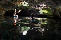 Two boys enjoy a fresh water cave at Queen's Bath at Kiholo Bay, Big Island.