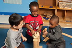 Education Preschool 3-4 year olds group of three boys building with wooden blocks together