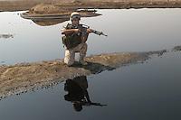"""- Italian military intervention in Iraq (10/2004), a soldier of the aiborne brigade """"Friuli"""" controls a pool of oil in the desert of Dhi Qar region,  provoked by smugglers of fuel that do leaks in the oil pipe-line<br /> <br /> - un militare della brigata aeromobile """"Friuli"""" controlla una pozza di petrolio nel deserto della regione di Dhi Qar provocata da contrabbandieri di carburante che praticano falle nell'oleodotto"""