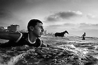 17 year old surfer Amer Aldos paddles out into the Mediterranean Sea from Gaza City, as a man washes his horse in the water.