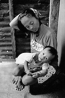 Philippines. Luzon Region. Manila. Tondo area. Smokey mountain is a rubbish dump. Life on a garbage heap. A mother holds her malnourished child in her arms.  © 1992 Didier Ruef .