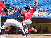 Quad Cities River Bandits Oscar Taveras #15 slides into home past catcher Alex Monsalve #30 during a game against the Lake County Captains at Classic Park on July 21, 2011 in Eastlake, Ohio.  Lake County defeated Quad Cities 16-15.  (Mike Janes/Four Seam Images)