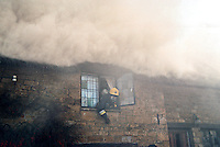 Firefighters, in breathing apparatus, are searching through a thatched house on fire. The firefighter is leaning out of the window to give instructions to other firefighters who are entering the house. This image may only be used to portray the subject in a positive manner..©shoutpictures.com..john@shoutpictures.com