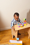Toddler boy throwing block into box, cleaning up