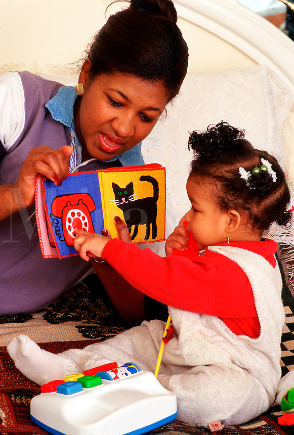 Asian-American mother and toddler daughter playing with telephone and looking at a book