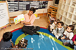 Education preschool 2-4 year olds circle time female teacher reading picture book to class horizontal