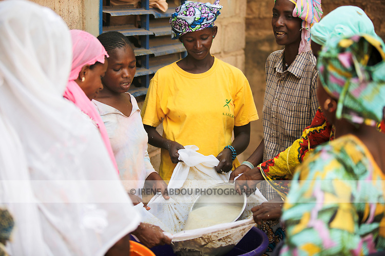 In Burkina Faso, West Africa, Muslim families celebrate the birth of a child on the 7th day after birth.  Women throughout Ouagadougou - friends and family - congregate at the mother's house on the morning of the baptism to help cook for guests.  Here, women strain water through millet to make a traditional millet drink.