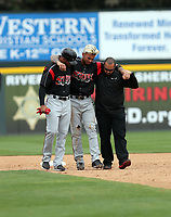 Gabriel Arias of the Lake Elsinore Storm is helped off the field by coach Felipe Blanco and trainer Ricky Huerta after injuring his ankle on a slide into second base during a game against the Rancho Cucamonga Quakes at LoanMart Field on April 30, 2019 in Rancho Cucamonga, California (Bill Mitchell)