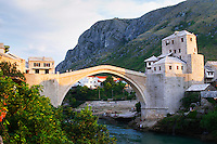 Sunset late afternoon light. View along the river of the old reconstructed bridge. Historic town of Mostar. Federation Bosne i Hercegovine. Bosnia Herzegovina, Europe.
