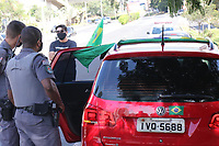 Campinas (SP), 01/05/2021 - Trabalho-SP - Um homem em um veículo com a bandeira do Brasil, retirou uma faixa pendura no viaduto colocado por manifestantes, armado o homem que se identificou como policial federal devolveu a faixa somente com a presença da Polícia Militar. Manifestantes realizam uma carreata e bicicletada no centro de Campinas, interior de São Paulo, neste sábado (01) em comemoração ao dia do trabalho. O ato também pedia mais vacina e a saída do presidente Jair Bolsonaro.