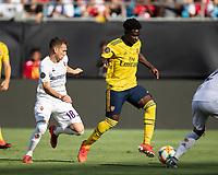 CHARLOTTE, NC - JULY 20: Bukayo Saka #77 advances with the ball as Sebastian Cristoforo #18 pursues during a game between ACF Fiorentina and Arsenal at Bank of America Stadium on July 20, 2019 in Charlotte, North Carolina.