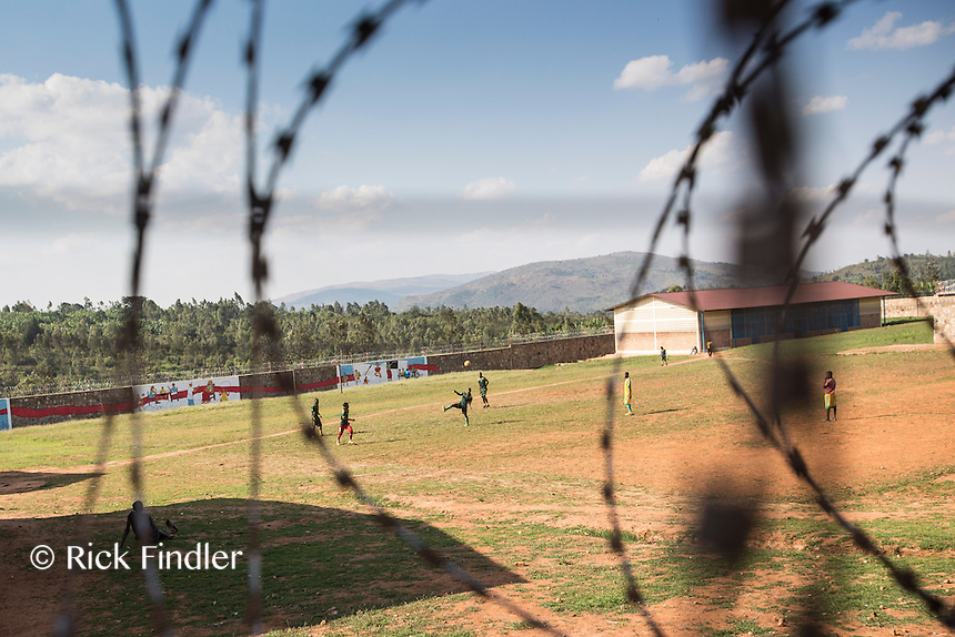 BURUNDI, Ruyigi: 10 June 2015 Ruyigi Re-education Centre Feature.<br /> See accompanying article for general information. <br /> Pictured: Boys can be seen playing football through the barbed-wire perimeter of the centre. <br /> Rick Findler / Story Picture Agency