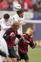 New England Revolution's Jay Heaps and Joe-Max Moore go up for a header over the top of MetroStars' Eddie Gaven and Ricardo Clark. The New England Revolution played the NY/NJ MetroStars to a 1 to 1 tie at Giant's Stadium, East Rutherford, NJ, on April 24, 2004.