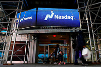 NEW YORK, NEW YORK - MARCH 10: People walk in front of Nasdaq building at Times Square on March 10, 2021, in New York. The Nasdaq Composite continued falling more than half a percent during the day also the move away from Apple Inc, Amazon.com Inc , Facebook Inc, Tesla Inc and Microsoft Corp, falling during the day, helped small-cap stocks rise more than double the gains of the S&P 500. (Photo by John Smith/VIEWpress)