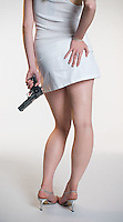 Lower body of Caucasian blonde woman facing away from camera  holding handgun on white seamless<br />
