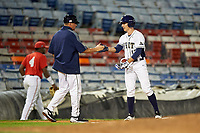 Pitt Panthers third base coach Bryan Peters high fives left fielder Jacob Wright (13) during a game against the Ohio State Buckeyes on February 20, 2016 at Holman Stadium at Historic Dodgertown in Vero Beach, Florida.  Ohio State defeated Pitt 11-8 in thirteen innings.  (Mike Janes/Four Seam Images)