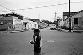 New Orleans, Louisiana.USA.July 28, 2006..Children in the 7th ward eat ice cream in the streets that now have a fraction of the population returning to live. This region was heavily damaged one year earlier hurricane Katrina hit and the levees broke leaving 80% of the city flooded. Within hours of this photo a quadruple homicide took place a few blocks from this street...