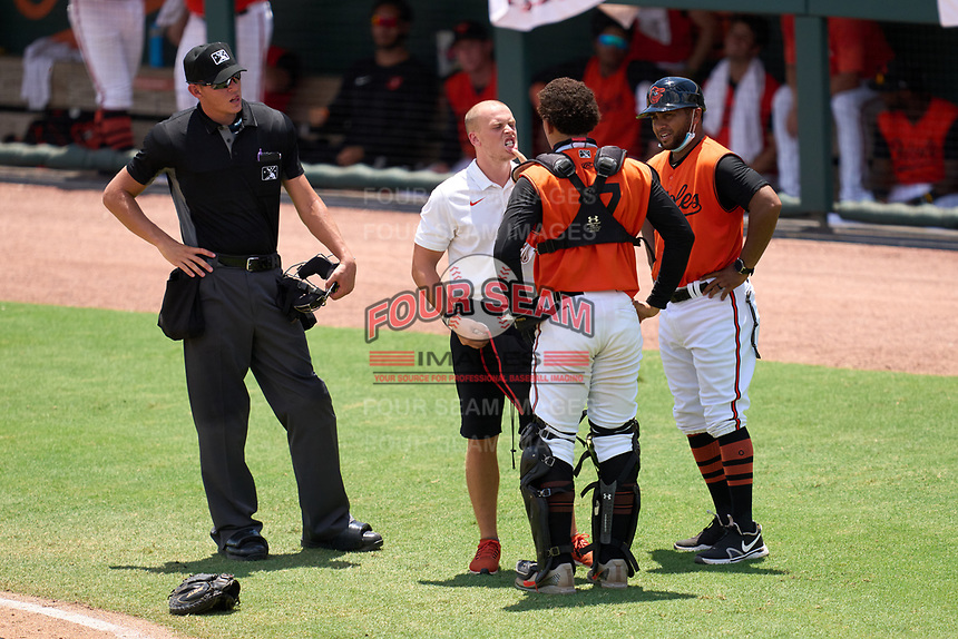 FCL Orioles Orange coach Christian Frias (right) and athletic trainer xxxx check on catcher Ricardo Rivera (17), as umpire Chase Eubanks looks on, during a game against the FCL Pirates Gold on August 9, 2021 at Ed Smith Stadium in Sarasota, Florida.  (Mike Janes/Four Seam Images)