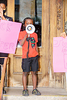 """Rally organizer Naheem Benalfew, 7, speaks to the crowd at the start of the """"Peaceful Children's March: Be the Change"""" demonstration in support of Black Lives Matter in Boston, Massachusetts, on Sun., June 7, 2020. The children's march was organized by siblings Naheem, 7, and Anaysha Benalfew, 10. The demonstration is part of a weeks-long nationwide response to the killing of George Floyd by Minneapolis police on May 25, 2020. The march started near the Nubian Square bus depot and continued to the nearby Boston Police Department headquarters, where marchers knelt for 8 minutes and 46 seconds, the time that police officers knelt on George Floyd's neck during his killing. A number of children, mostly people of color, then spoke about how people should be treated equally and how they wished they didn't have to grow up fearful that a police officer would kill them or their loved ones.  The signs here read """"Black Lives Matter"""" and """"just for Floyd."""""""