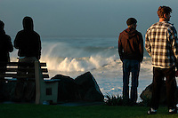 Surfers watch in awe as 10 to 18 foot (3 ? 6 m) waves break over PB point at dawn in San Diego, California, USA Wednesday, December 5, 2007.  A large storm swell brought the unusually high surf to the area, testing the skill and endurance of surfers and breaking numerous surfboards throughout the day.