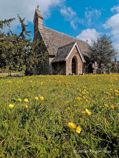 Exterior of St Lawrence Church, Tubney, Oxfordshire, UK in May sunshine. Many wild flowers such as the buttercup grow in the surrounding ground which has not been subject to chemical fertilisers, weedkillers and pestcides since the consecration of the church in 1847. This is the only Protestant church designed by Augustus Pugin who also designed the interior fittings.
