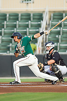 Yefri Perez (12) of the Greensboro Grasshoppers follows through on his swing against the Kannapolis Intimidators at CMC-Northeast Stadium on June 12, 2014 in Kannapolis, North Carolina.  The Grasshoppers defeated the Intimidators 5-2.  (Brian Westerholt/Four Seam Images)