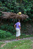 Bali, Indonesia.   Woman Carrying Palm Fronds and Coconuts on her Head.  Tenganan Village.