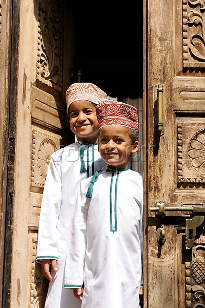 Oman, Muscat: Omanische Jungen vor einer alten Haustuer. 2010, Kinder, Kind, Junge, Tuer, Schnitzereien, traditionell, traditionelle Kleidung, Arabische Halbinsel, HF; <br /> <br /> (Bildtechnik: sRGB, <br /> 69.77 MByte vorhanden)<br /> <br /> English: Oman, Muscat, Omani boys, old carved wooden door, 2010, locals, children, traditional clothing, Arabian Peninsula