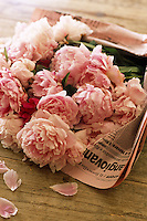 A bunch of peony roses picked from the garden and wrapped in newspaper on a wooden table