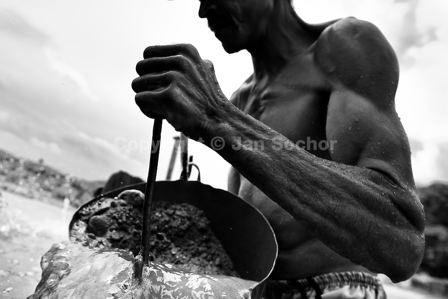 A Colombian sand miner unloads a bucket full of sand into his boat anchored in the middle of the river La Vieja in Cartago, Colombia, 15 April 2013. Artisanal (unmechanised) sand mining is an ancient mining technique used to obtain sand for construction purposes. Depending on the natural conditions (strength of the stream, depth of the river etc.), together with the sand miners' physical condition, the material is extracted in metal buckets, either by standing on the river bottom and searching for sand by feet, or, diving up to 3-5 meters deep using a wooden plank with steps. In spite of the physically demanding work, a sand miner's daily salary does not exceed 15-20 US dollars. However, the sand miners are very proud of their profession, valuing their work freedom above all, and usually, as long as their health and strength permit, they keep facing the river stream.