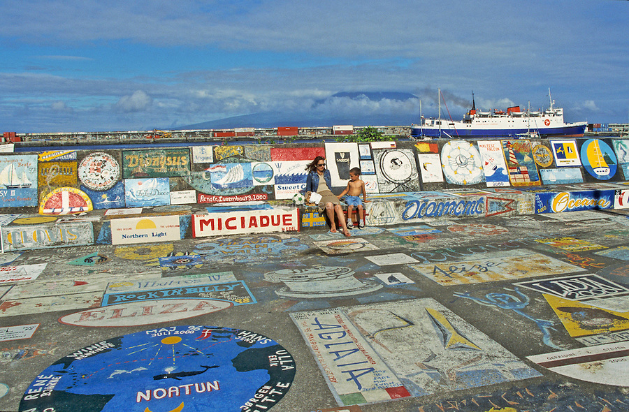 colorful paintings on the walls and sidewalks of the marina's jetty of Horta. Faial Island