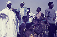 Sallah festivities in Bauchi. A group of standing Muslim men in white with non-Muslim sitting women watching, with bare shoulders outside. between 1970 and 1973