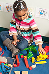 Education preschool 3 year olds girl sitting on floor sorting blocks by color and stacking them