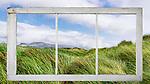 Outside a vintage window, windblown graass on ocean dunes, Nehalem Bay, Nehalem Bay State Park, Oregon.  Between the Pacific Ocean and Nehalem Bay, looking north to Manzanita, Oregon