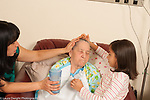 9 year old girl at home with mother and grandmother helping to feed grandmother on liquid diet due to Alzheimer's disease horizontal