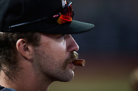 Aberdeen IronBirds pitcher Drew Rom (12) enjoys a meat stick during the game against the Hudson Valley Renegades at Leidos Field at Ripken Stadium on July 23, 2021, in Aberdeen, MD. (Brian Westerholt/Four Seam Images)