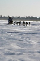 Saturday March 10, 2007   ----   Paul Gebhart sits behind his sled as he runs on the Yukon River on Saturday between Eagle Island and Kaltag in 35-45 mph wind.