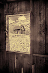 Abandoned house through the window of another abandoned house in a ghost town