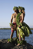 Kane (male) and wahine (female) hula dancers wearing palapalai fern head lei look out to sea.