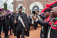 """Nigeria. Enugu State. Ukana. Saint Joseph's Catholic Parish. Igbo funeral of Dr William Ikechukwu who passed away at the age of 68 years old. At the end of the mass, the white coffin carried by bearers is greeted outside of the church by a group of men, wearing black uniforms, tricorne hats and holding their swords up in the air. The men are all members of """" The Knights of Saint Mulumba"""" (KSM), an order which was established in Nigeria on June 14, 1953 by Late Reverend Father Abraham Anselm Isidahome Ojefua; a Priest and Monk from Illah Monastery and modelled after the Sacred Order of Catholic Knighthood. It has a current membership of over 20,000 (both male and female). The initial objectives of the order are: To counteract the harm done by many secret societies to the church and to arrest the efflux of the Christian enlightened members into those harmful secret groups. To bring Catholics together in a fraternal association for the good and progress of the church, welfare of its clergy, wellbeing of members of the Order in particular and Nigeria in general. The constitution has been review severally and emphasis is now on fostering perfect Christian life among members, making the Order Africa – wide and encouraging inter religious dialogue. 5.07.19 © 2019 Didier Ruef"""